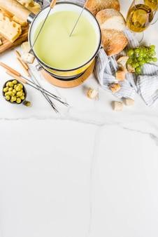 Fondue suisse gastronomique dans un plat à fondue traditionnel, avec fourchettes, divers fromages, olives, pain et raisin