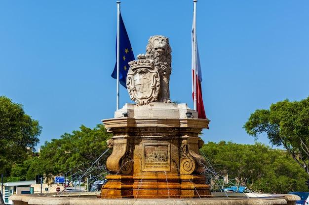 Une fontaine baroque avec un grand lion en calcaire qui garde sa patte sur dado avec l'image sculptée.