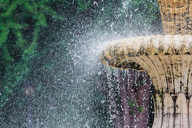 Fontaine d'eau dans le parc. éclaboussures de ruisseaux de fontaine dans le ruisseau d'eau qui coule de la fontaine. l'eau de la fontaine éclabousse sur la surface de l'eau du lac du parc. fontaine dans le parc d'été.