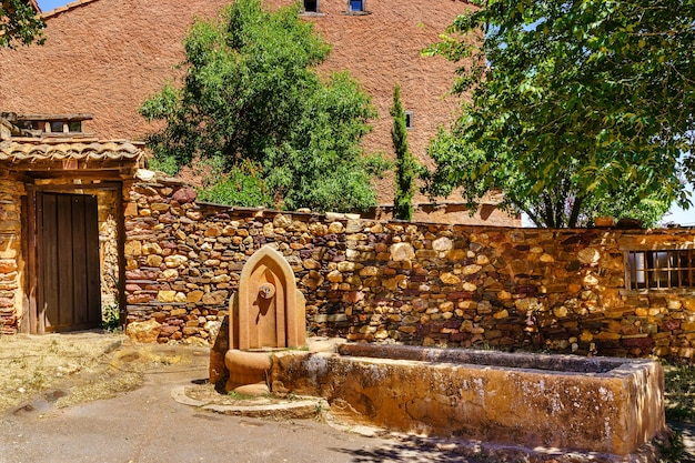 Fontaine d'eau douce à l'entrée d'une ancienne maison en pierre.