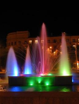 Fontaine illuminée par des lanternes multicolores la nuit