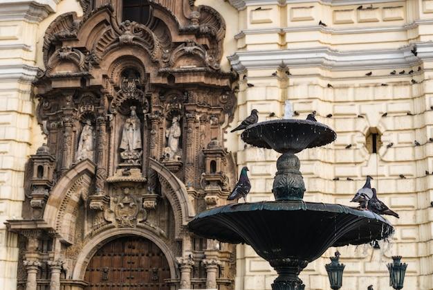 Fontaine avec des pigeons en face de l'église de san francisco dans le centre historique de lima