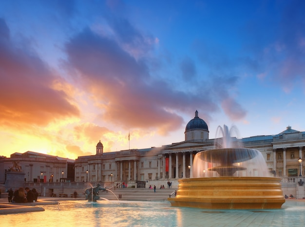 Fontaine sur trafalgar square sur un coucher de soleil avec le bâtiment de la national gallery