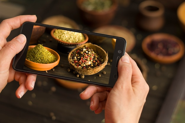 Food-blogger prend des photos sur un smartphone épices pour les réseaux sociaux.