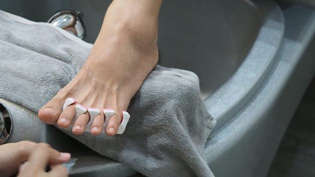 Foot spa femme pieds nus massant dans de l'eau savonneuse machine au spa shop pieds de femmes entrant dans le bain