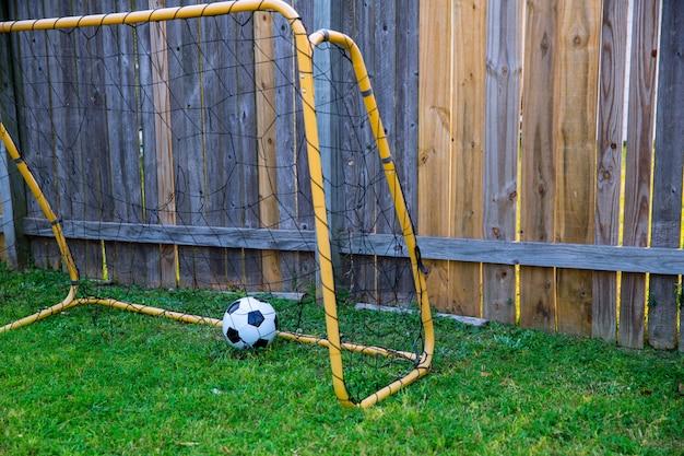 Football des enfants dans la cour à la clôture en bois avec mur