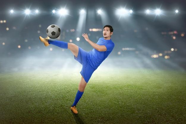 Footballeur asiatique excité montrant ses compétences