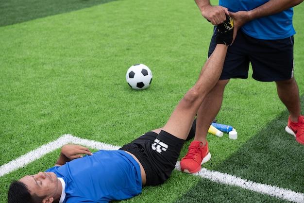 Footballeur vêtu d'une chemise bleue, un pantalon noir blessé dans la pelouse pendant la course.