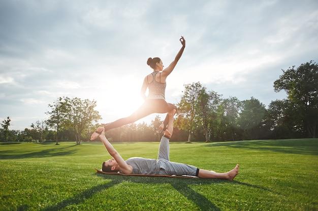 Force et flexibilité couple jeune et en bonne santé faisant du yoga acro dans la nature sous le soleil