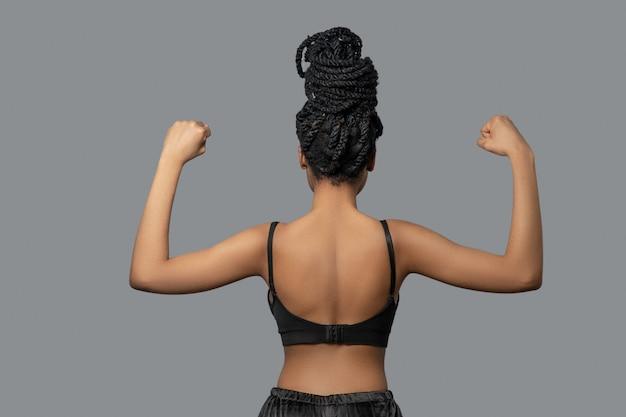 Force. mignonne mulâtre en noir montrant ses muscles de l'arrière