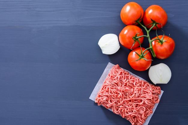 Forcemeat avec des tomates rouges sur une branche et des oignons émincés sur un fond en bois gris avec espace de copie