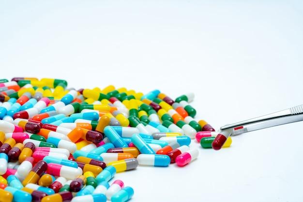 Les forceps choisissent la capsule rouge-blanche du groupe de pilules de capsule.