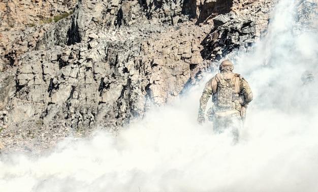 Forces spéciales en action dans le désert parmi les rochers couverts par un écran de fumée