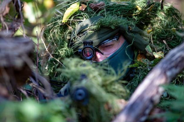 Forces spéciales, fusil d'assaut de soldat avec silencieux, viseur optique. derrière le couvercle en attente d'embuscade