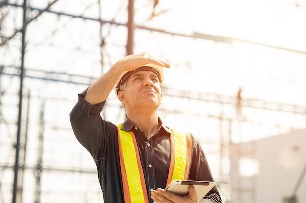 Foreman builder ingénieur travailleur regardant grand chantier de construction journée ensoleillée de travail acharné.