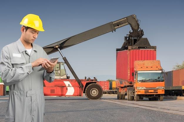 Foreman stand check tablet sur le chargement du chariot élévateur avant la boîte de conteneurs pour la logistique d'importation de fret d'exportation
