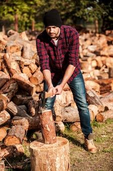 Forestier qualifié. toute la longueur du journal de coupe de jeune forestier confiant tout en se tenant à l'extérieur