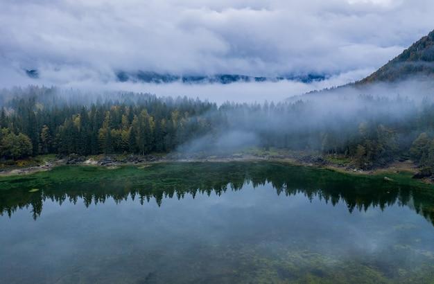 Forêt brumeuse et brumeuse au lac fusine en italie