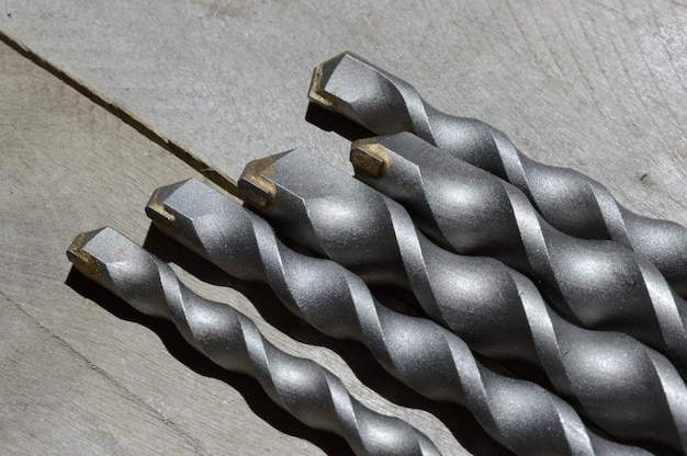 Les forets avec pointe en carbure pour perceuse à percussion se trouvent sur un fond en bois de planche. fermer.