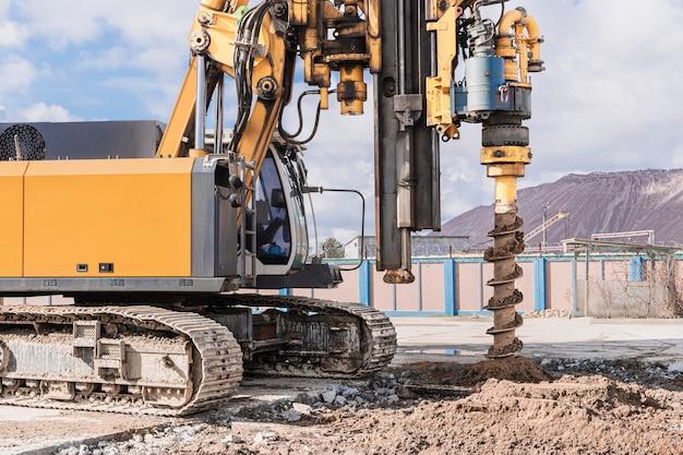 Foreuse hydraulique puissante sur un chantier de construction. pose de pieux forés par forage. fondations sur pieux. forage dans le sol.