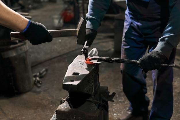 Le forgeron avec l'attaquant forge un fer à cheval sur l'enclume avec le ciseau de forge, plan rapproché