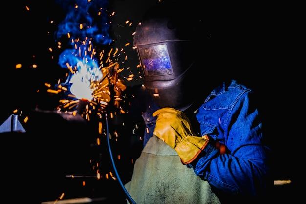 Forgeron au travail et portant un masque de protection.