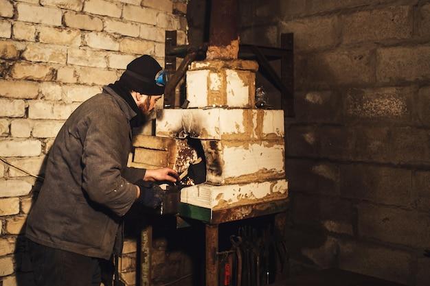 Le forgeron barbu allume un feu dans le four