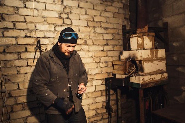 Le forgeron barbu allume le feu avec de la pierre à feu et du silex
