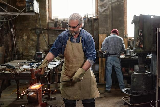Forgeron barbu mature en tablier travaillant avec du fer dans l'atelier avec son collègue en arrière-plan