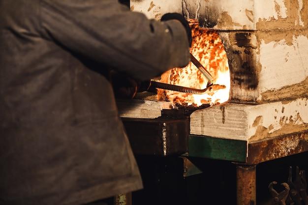 Un forgeron barbu sort une billette chauffée au rouge du four.