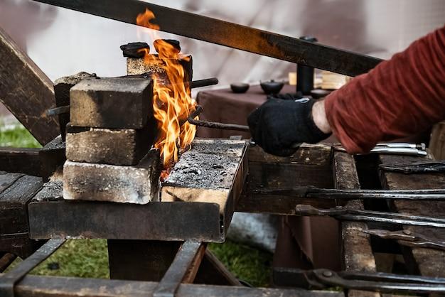 Le Forgeron Chauffe Le Produit En Métal Dans Le Feu De La Forge Photo Premium