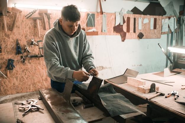 Le forgeron ferblantier utilise un marteau travaillant dans son atelier.