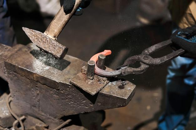 Le forgeron forge un fer à cheval sur l'enclume avec la dérive de flexion, plan rapproché