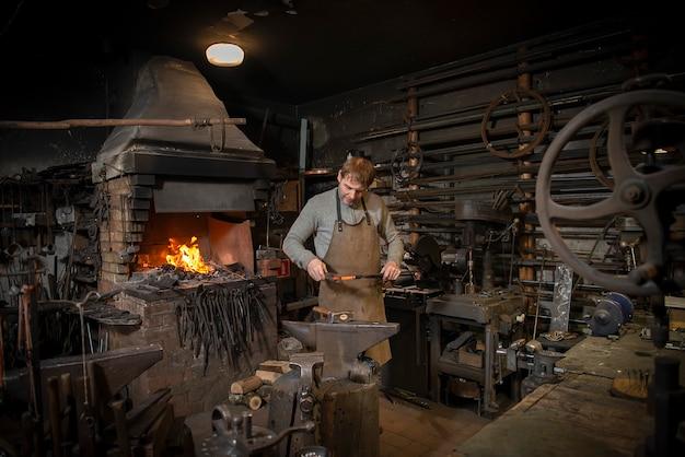 Le forgeron forge manuellement le métal rouge sur l'enclume dans la forge avec des feux d'artifice à étincelles