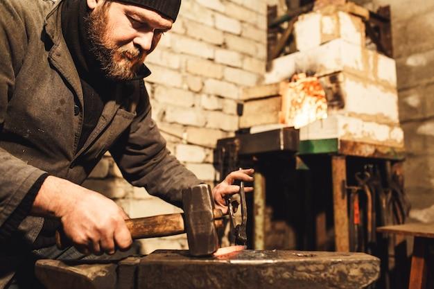 Forgeron forge un métal chaud sur l'enclume avec un marteau