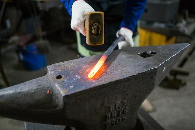 Le forgeron forge le métal lumineux dans le four, déclenche les étincelles