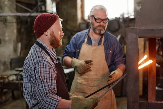 Forgeron forgeant le fer dans l'atelier