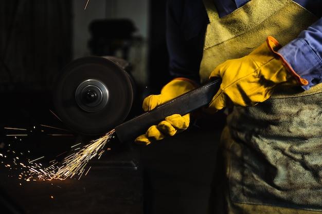 Le forgeron avec des gants jaunes fait des étincelles avec une machine dans l'atelier