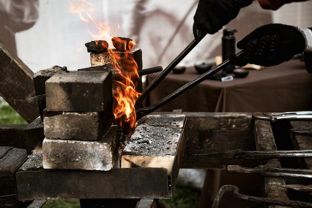 Le forgeron prend le produit en métal redhot du feu avec la pince