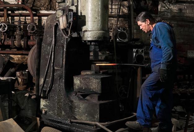 Le forgeron traite une pièce chaude avec un marteau électrique dans un atelier