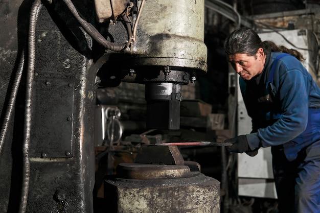 Le forgeron traite une pièce chaude avec un marteau de machine dans un atelier