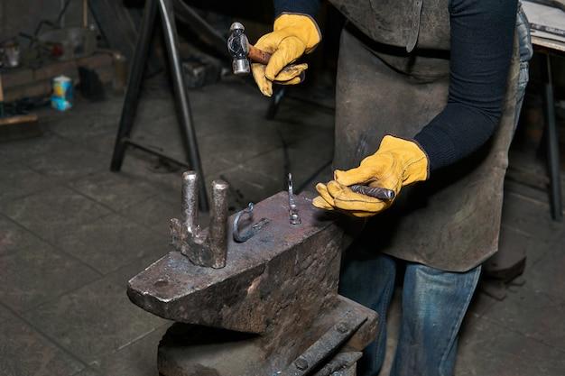 Un forgeron traite des produits d'art sur une enclume avec un ciseau et un marteau