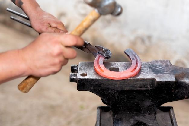 Forgeron travaillant sur l'enclume, faisant un fer à cheval.