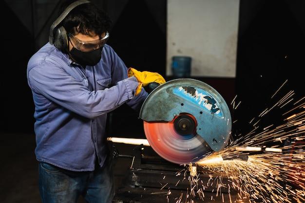 Forgeron en vêtements de travail et gants jaunes broyant une plaque de métal