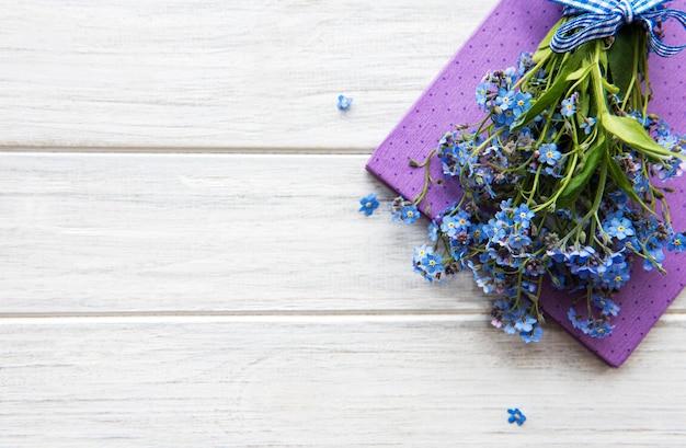 Forget-me-not fleurs et cahier sur une table en bois blanc