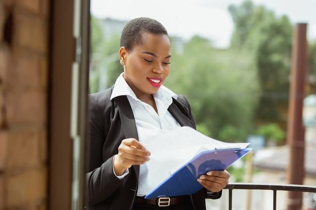 Formalités administratives. femme d'affaires afro-américaine en tenue de bureau souriante, a l'air confiante et heureuse, occupée. concept de finance, d'entreprise, d'égalité et de droits de l'homme. belle jeune femme modèle, réussie.