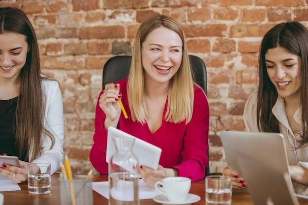 Formalités administratives. jeune femme d'affaires dans un bureau moderne avec équipe. réunion créative, attribution de tâches. les femmes travaillant au front-office. concept de finance, d'affaires, de pouvoir des filles, d'inclusion, de diversité, de féminisme.