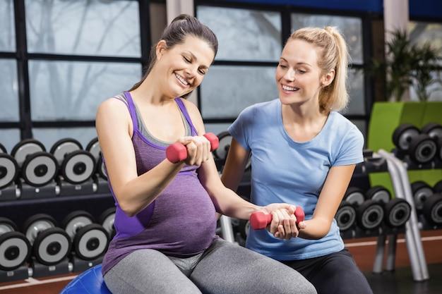 Formateur aidant une femme enceinte au gymnase avec haltère