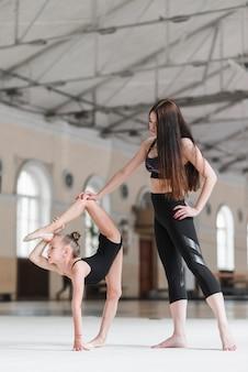 Formateur aidant son élève de ballerine qui s'étend sur la piste de danse