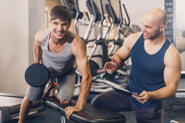 Le formateur aide l'homme à faire l'exercice.